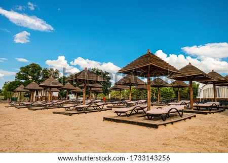 Brown wooden loungers and umbrellas on empty sandy beach. Rows resting places in the failed tourist season. #1733143256