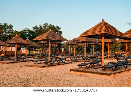 Brown wooden loungers and umbrellas on empty sandy beach. Rows resting places. #1733143757