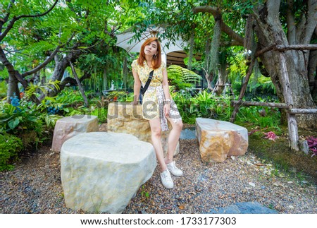 Woman wear her yellow dress standing and prepare to go to picnic and posting for take a portrait picture in the garden.