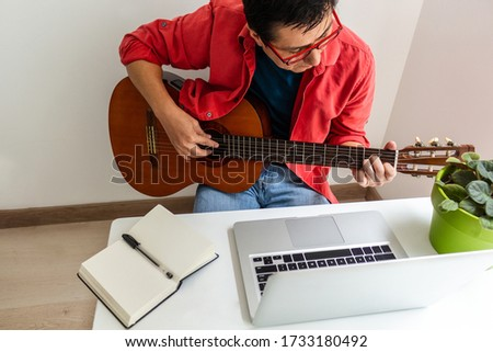 In a room at home a man plays the guitar in front of his laptop during an online class Royalty-Free Stock Photo #1733180492
