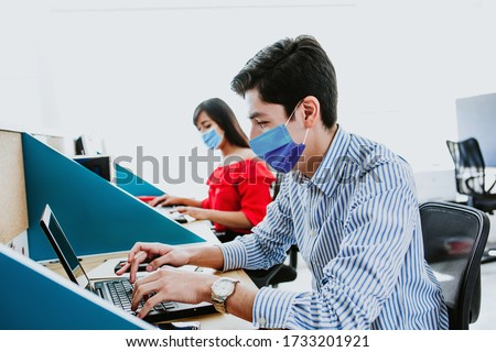 Latin People working in business office wearing medical face mask for social distancing in new normal situation protecting and preventing the infection of corona virus or covid-19 in Latin America  #1733201921