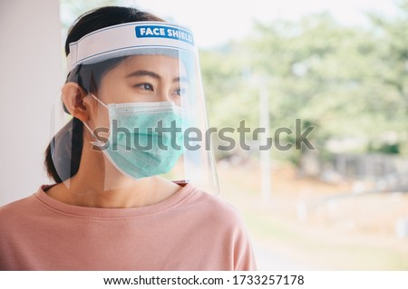 Asian woman wearing mask and face shield before going outside her room for prevent and protection covid-19 virus disease. Conceptual of new normal lifestyle after Covid-19 pandemic outbreak. #1733257178