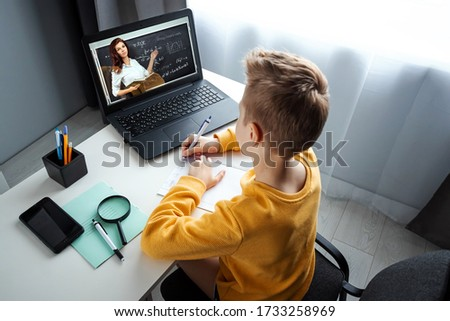 A child, a boy in a yellow jacket, is sitting at a table at home looking at a laptop, online learning, distance learning at home via the Internet. Technology, school, knowledge. Copy space Royalty-Free Stock Photo #1733258969