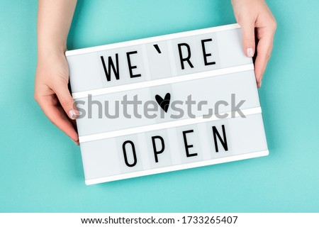 Lightbox with the text We're Open on a blue background in women's hands.