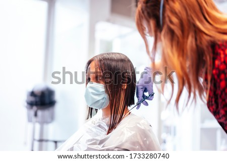 Hairdresser with mask and gloves cutting the ends of the hair to the client. Reopening with security measures for hairdressers in the Covid-19 pandemic Royalty-Free Stock Photo #1733280740