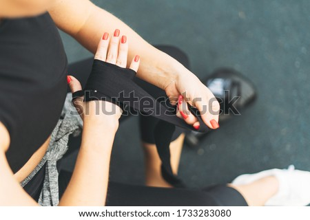 Crop photo of young athletic girl shakes boxing bandages on hands before training Royalty-Free Stock Photo #1733283080