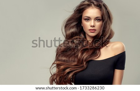 Brunette  girl with long , healthy and   shiny curly hair .  Beautiful  model woman  with wavy hairstyle   .Care and beauty  Royalty-Free Stock Photo #1733286230