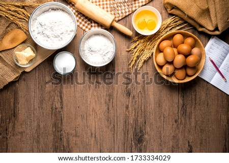 Pictures of ingredients for making cakes bakery around, such as eggs, flour, sugar, butter, recipe book and equipment for making on a wooden floor, with copy space.