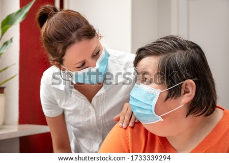 Mentally disabled woman and nurse or caretaker wearing a surgical mask, covid-19 or corona, coronavirus and handicapped people #1733339294