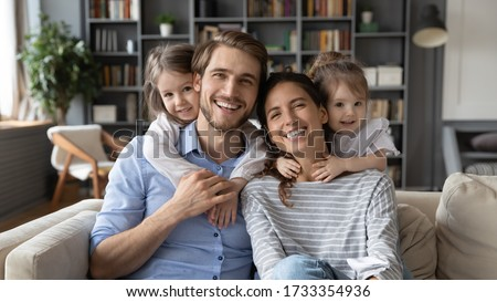 Portrait of young Caucasian family with small daughters pose relax on sofa in living room, smiling little girls kids hug embrace parents, show love and gratitude, rest on couch at home together