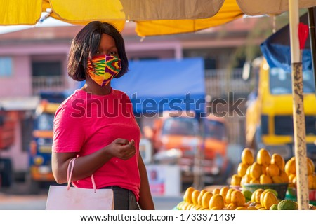 A beautiful African girl buying from local market and wearing a face mask for protection - concept on black millennial buying from market during covid-19 pandemic - Africa fruits and veggies market.  #1733371439