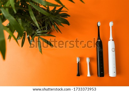 Modern black and white sonic or electric toothbrush on flat lay orange background. Concept of professional oral care and healthy teeth by using smart sonic toothbrush. Minimal design