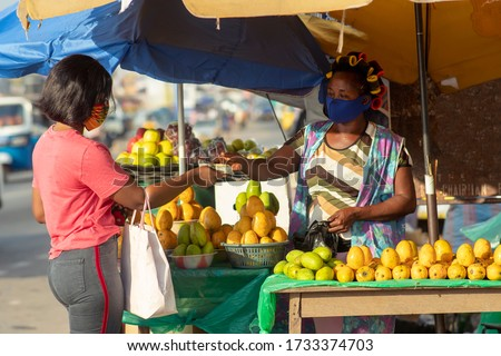 Young black woman paying money to a fruit vendor for a purchased item in the market. Two women wearing locally made masks on the street in covid-19 pandemic season for protection - Marketing in Africa #1733374703