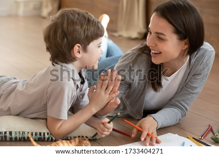 Overjoyed young mother and small preschooler son give high five playing drawing together, happy mom or nanny have fun painting on paper learning with little boy child at home, education concept