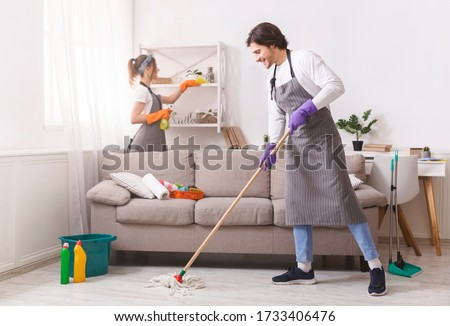 Residential Cleaning Services. Couple Of Skilled Housekeepers Man And Woman Tidying Up Apartment, Doing Household Together, Free Space Royalty-Free Stock Photo #1733406476