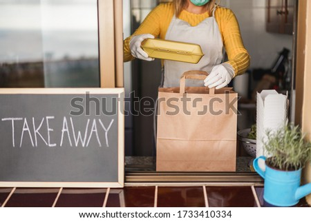Young woman preparing takeaway organic food inside restaurant during Coronavirus outbreak time - Worker inside kitchen cooking food for online delivery service - Focus on hands #1733410334