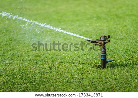Lawn sprinkler spraying water over green grass. Close-up picture. Water jet. Fresh green grass.