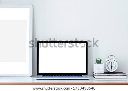 Mockup blank screen laptop, wooden picture frame, cuctus and alarm clock on white wooden table in contemporary room, copy space.