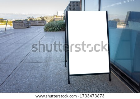 Blank white outdoor advertising stand/sandwich board mockup template. Clear street signage board placed on pedestrian sidewalk.