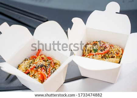 Closeup tasty food wok in box delivery. Udon noodles with tempuru, shrimps, soy sauce. Japanese spicy food in disposable eco boxes. 1+1 wok box udon advertise. 2 wok in box. #1733474882