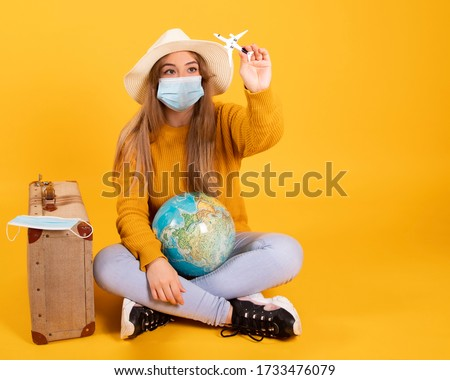 A tourist girl with a medical mask, outbreak of coronavirus COVID-19. Concept of canceled trips. A tourist cannot leave due to a pandemic. Royalty-Free Stock Photo #1733476079