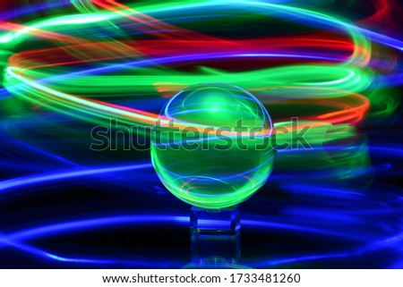 An abstract picture of a crystal ball with neon colorful spiral lights