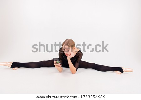 Picture of a beautiful caucasian woman in a black gymnastics suit sits on the floor in a twine