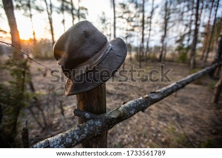 An old hat hangs on a fence in a pine forest.  The hat is in focus and the background is blurry.  Sunset.  Hats from shots are visible on the hat.  target hat #1733561789
