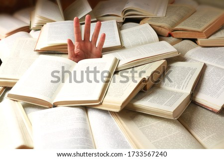 A student or reader drowned in a mountain of books. Man's hand sticks out from the rubble of open books. Concept - preparing for exams or excess information. Selective focus. #1733567240