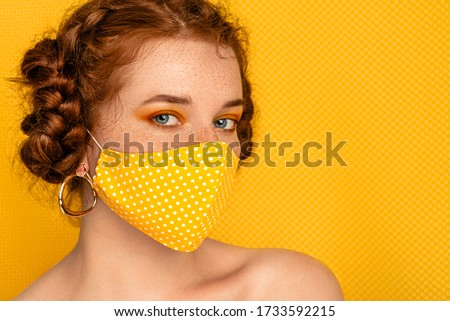 Redhead freckled woman wearing stylish handmade protective yellow polka dot cloth mask. Fashion during quarantine of coronavirus outbreak. Copy, empty space for text  #1733592215
