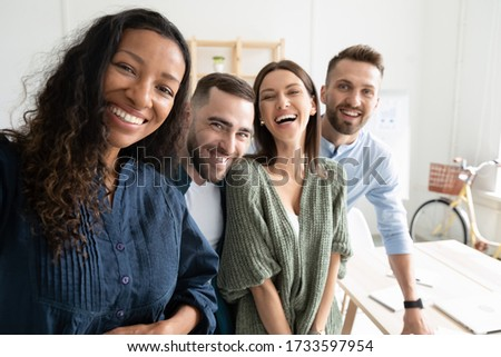 Close up headshot portrait picture of diverse team taking selfie looking at camera. Happy confident millennial african amerucan woman manager with colleagues on workplace background in office.