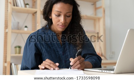 Close up young serious african american businesswoman sign up document at work. Tired black woman employee writing report on paper near modern laptop. Success business deal concept.