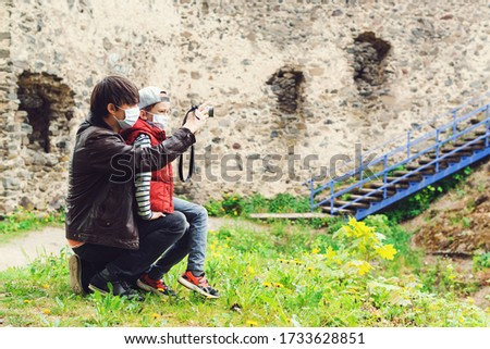 Father teaching his son to take pictures of old castle. Family trip to old castle. Coronavirus quarantine. Parents with son wearing face masks. Happy Father's day. Boy and dad spending time together.