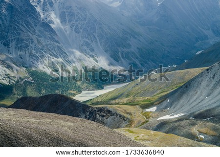 Awesome aerial view to beautiful valley with mountains lake and giant textured slopes with forest. Atmospheric alpine landscape with big rocky hills and huge mountains. Nature patterns on mountainside