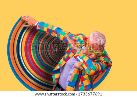 Old senior man performing dab dance moves. Concept about lifestyle and seniority. Isolated man on colored background and graphic effects