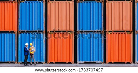 Panoramic of smart creative foreman and engineer woman control loading containers box from cargo freight ship for import export. Logistic, transportation, import and export concept. With copy space. Royalty-Free Stock Photo #1733707457
