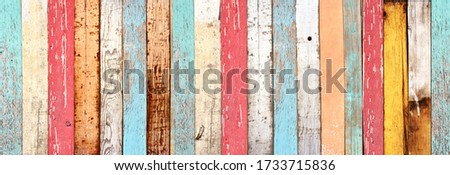 Texture of vintage wood boards with cracked paint of white, red, orange, yellow, cyan and blue color. Horizontal retro background with old wooden planks of different colors Royalty-Free Stock Photo #1733715836