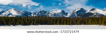 Panoramic view of the snow covered Rocky Mountains on a sunny, winter day with a forest and frozen lake view in Rocky Mountain National Park near Estes Park, Colorado #1733721479