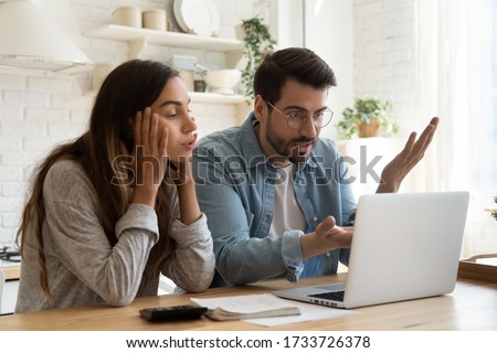 Mad millennial couple frustrated with slow Internet connection paying bills online in kitchen, confused young husband and wife angry with unexpected error mistake using internet banking on computer