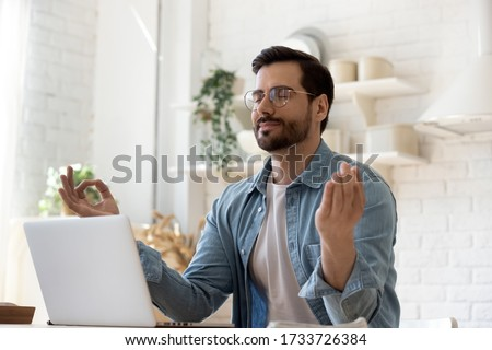 Calm millennial Caucasian man in glasses sit at table distracted from computer work meditate in kitchen, peaceful young male practice yoga relieve negative emotions at workplace, stress free concept Royalty-Free Stock Photo #1733726384