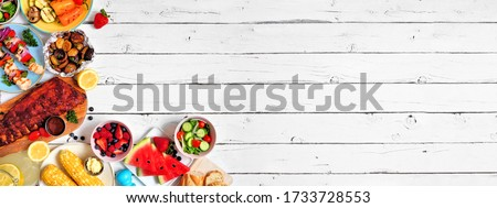Summer BBQ or picnic food corner border. Assortment of grilled meat, vegetables, fruits, salad and potatoes. Overhead view over a white wood background. Copy space.