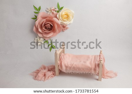 Spring pastel flowers on wall next to baby bed with decor in white baby's room, copy space concept. Stylish baby bed near light wall in interior of children's room. Bucket of rose flowers