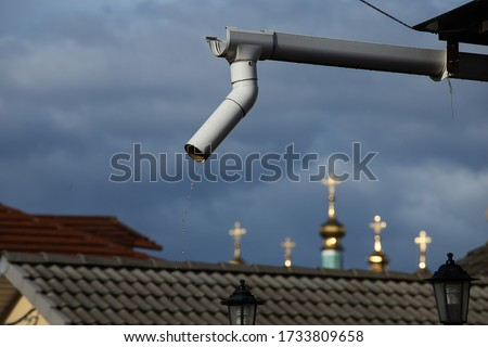 downspout on the roof of a private house, poorly organized drainage of rainwater from a height of pouring drops, against the background of storm clouds and the domes of the Church #1733809658