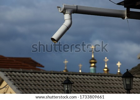 downspout on the roof of a private house, poorly organized drainage of rainwater from a height of pouring drops, against the background of storm clouds and the domes of the Church #1733809661