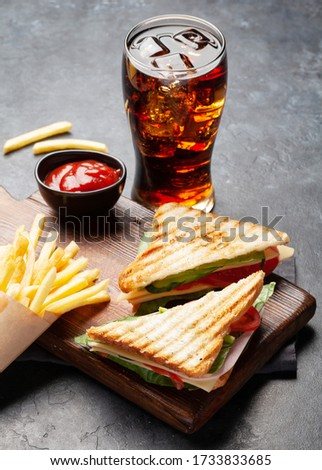 Club sandwich, potato fries chips and glass of cola drink with ice. Fast food take away #1733833685