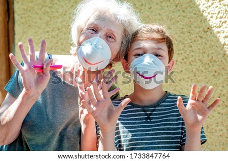 Happy laughing grandmother with grandchild in a respiratory masks plays together near house. Family fun. Stay at home. Drawing a smile on protective masks. Quarantin, isolated. Coronavirus covid-19. #1733847764