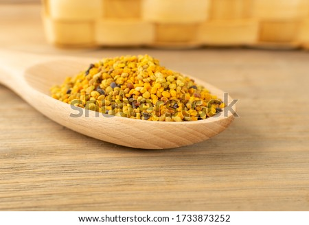 Macro shot of bee pollen or perga in wooden spoon on blurred rustic background. Raw brown, yellow, orange and blue flower pollen grains or bee bread. Healthy food supplement with selective focus Royalty-Free Stock Photo #1733873252