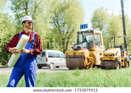 road construction workers near asphalt paver machine. Road repair. Road service worker near the rink. #1733879912