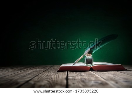 Quill pen and inkwell resting on an old book with green background concept for literature, writing, author and history #1733893220