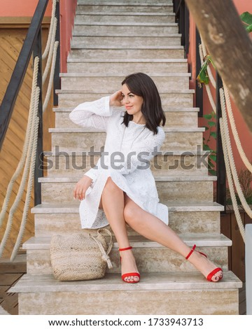 Beautiful brunette woman in white dress, red shoes and wicker bag sitting on the stairs.